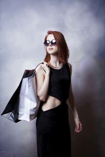 Style redhead girl with sunglasses and black dress with shopping bags on grey background