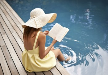 young woman relaxing at the pool with a book