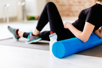 Fitness concept. Close up of woman relaxing after workout on the exercising mat..Portrait of Active Tired Woman Using Foam Roller in Light Room.
